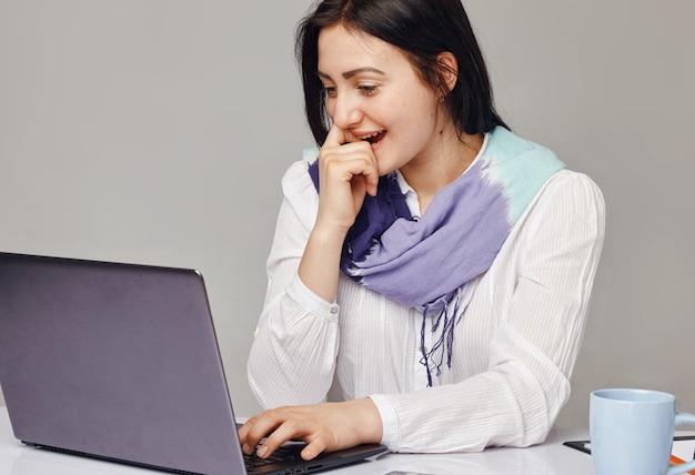 Szczęśliwy przedsiębiorca dorywczo pracujący online z laptopem w biurze