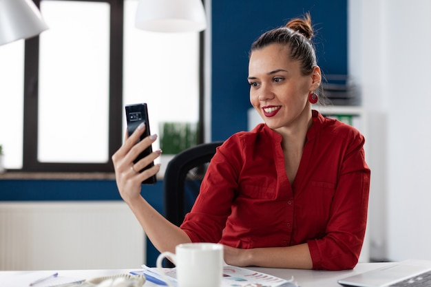Szczęśliwy przedsiębiorca w biurze firmy robi selfie za pomocą aparatu w smartfonie