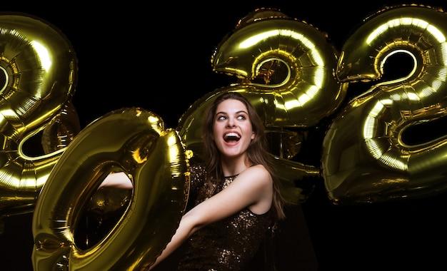 Szczęśliwy przepiękna dziewczyna w stylowej seksownej sukience trzymającej złote balony 2022, zabawy na boże narodzenie lub sylwestrową imprezę.