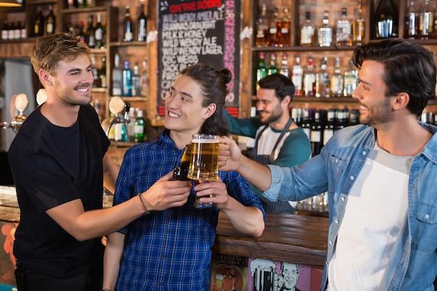 Szczęśliwy przyjaciół płci męskiej opiekania kufle do piwa i butelka