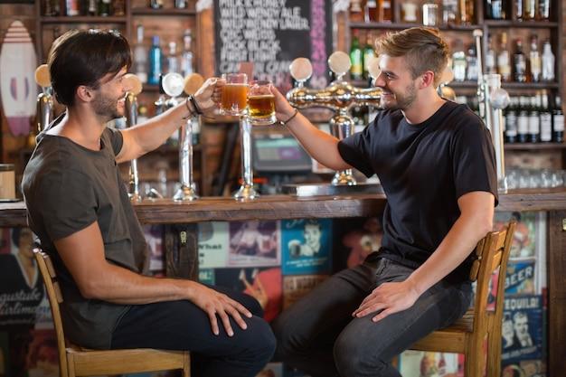 Szczęśliwy przyjaciół płci męskiej opiekania kufle do piwa w barze
