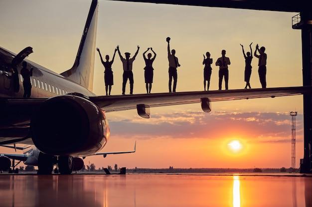 Szczęśliwy przyjazny, solidny zespół pilotów i stewardes na białym tle na tle zachodu słońca