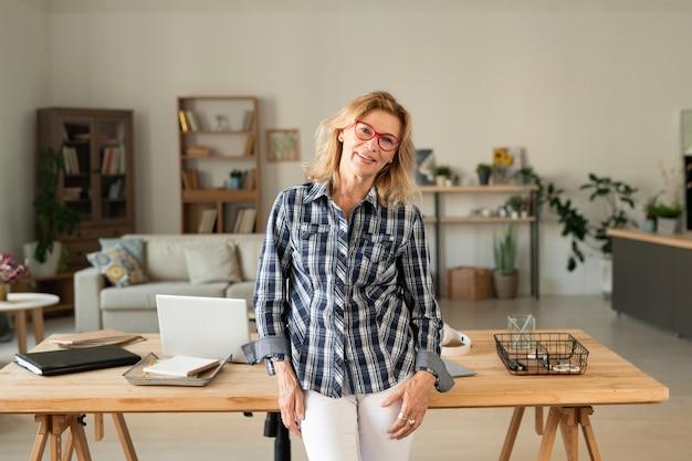 Szczęśliwy przypadkowy blond kobieta w średnim wieku w swoim miejscu pracy ze stołem, laptopem, materiałami i dokumentami w domu