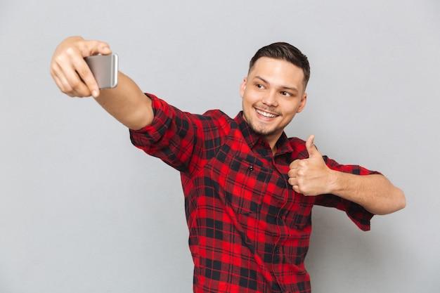 Szczęśliwy przypadkowy mężczyzna w szkockiej kraty koszula robi selfie