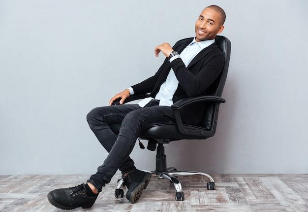 Szczęśliwy przystojny afroamerykanin młody człowiek siedzący
