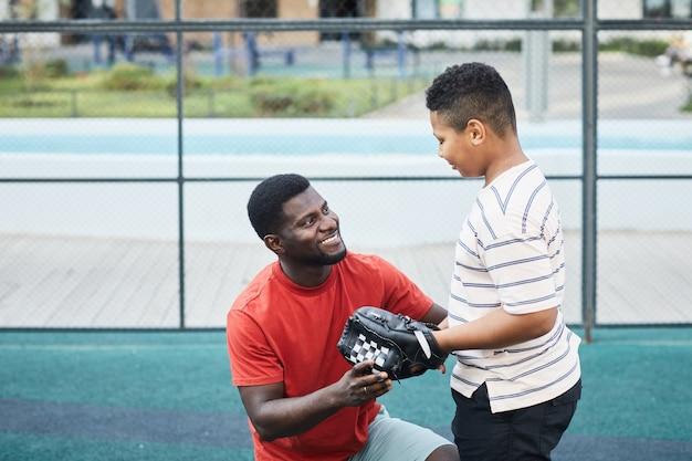 Szczęśliwy przystojny afroamerykanin z brodą rozmawiający z nastoletnim synem w rękawicy baseballowej, przygotowując go do gry