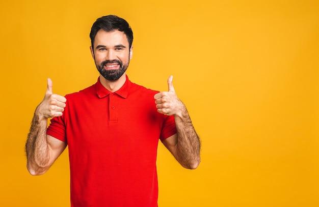 Szczęśliwy przystojny brodaty mężczyzna pokazuje kciuki do góry na białym tle na żółtym tle.