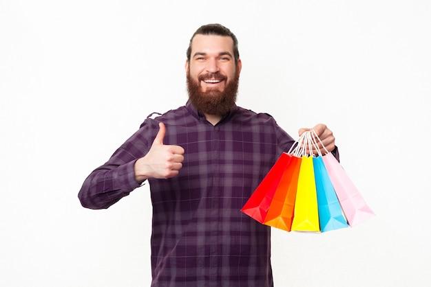 Szczęśliwy przystojny brodaty mężczyzna w kraciastej koszuli pokazując kciuk do góry i trzymając kolorowe torby na zakupy