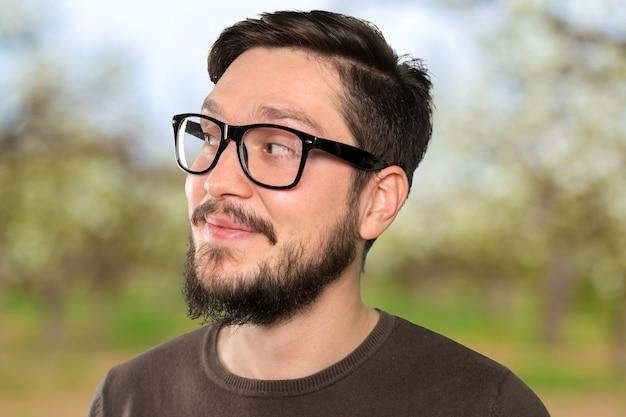 Szczęśliwy przystojny brodaty mężczyzna w przypadkowych ubraniach