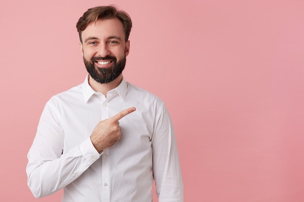 Szczęśliwy przystojny brodaty młody człowiek, ubrany w białą koszulę. chce przekazać fajne wiadomości. szeroko uśmiechnięta, zwraca uwagę na miejsce po prawej stronie; pojedynczo na różowym tle.