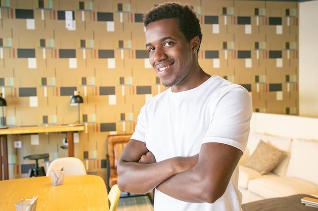 Szczęśliwy przystojny facet afroamerykanin pozowanie z rękoma we wnętrzu co-working lub kawiarnia, patrząc na kamery i uśmiechnięty