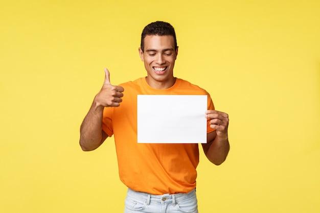 Szczęśliwy przystojny facet hiszpanin w pomarańczowy t-shirt, trzymając pusty papier
