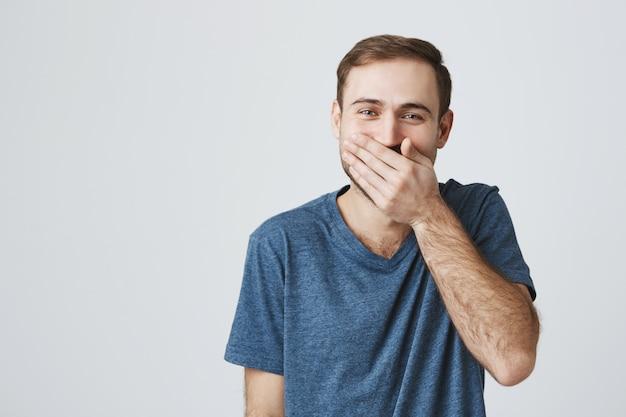 Szczęśliwy przystojny facet, śmiejąc się, zakrywając usta dłonią