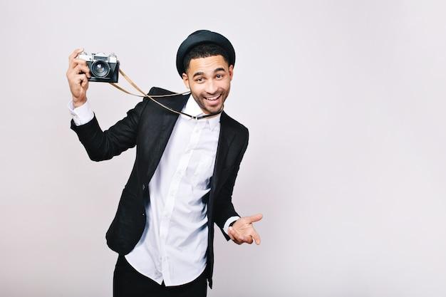 Szczęśliwy przystojny facet w garniturze, kapelusz, zabawy z aparatem. podekscytowany, wyrażający prawdziwe pozytywne emocje, uśmiechnięty, podróżujący, fotograf, sukces.