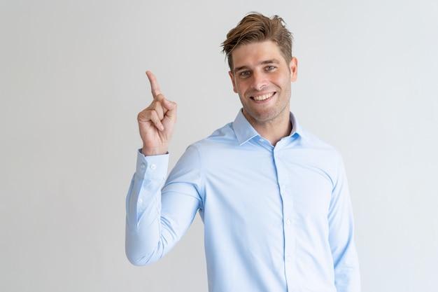 Szczęśliwy przystojny facet wskazuje upwards i patrzeje kamerę
