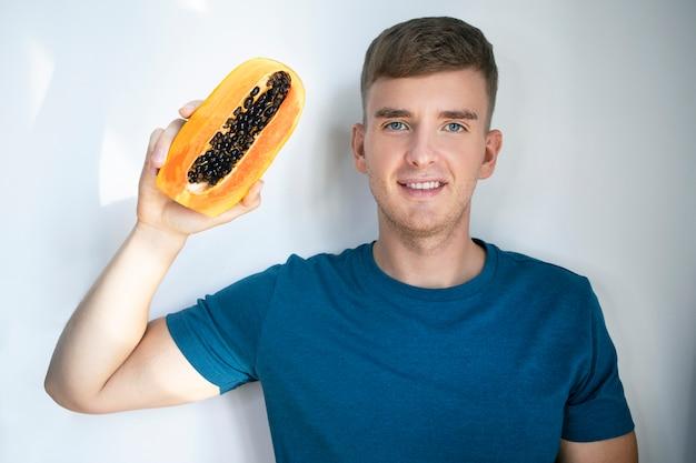 Szczęśliwy przystojny facet z owocami w ręku, młody człowiek trzyma świeżą dojrzałą połowę papai, uśmiechając się. wegańska lub wegetariańska, koncepcja zdrowej żywności