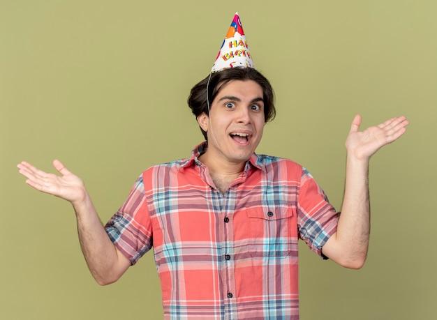 Szczęśliwy przystojny kaukaski mężczyzna w czapce urodzinowej stoi trzymając ręce otwarte hands