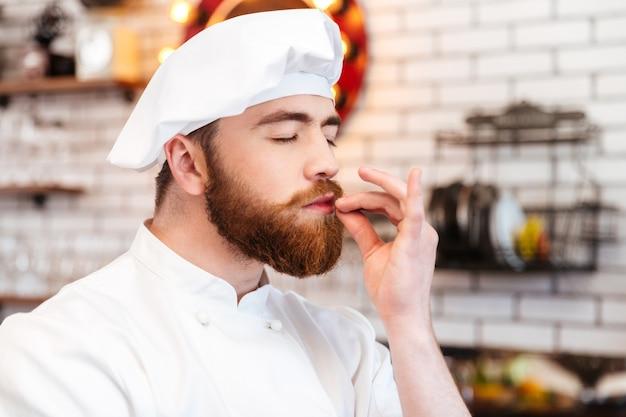 Szczęśliwy przystojny kucharz pachnący aromatem jedzenia w kuchni