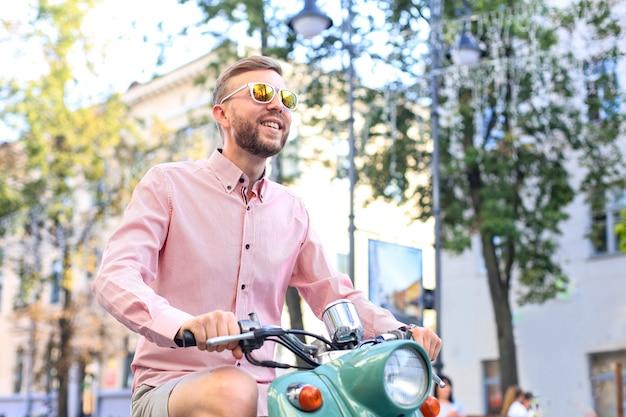 Szczęśliwy przystojny mężczyzna jazda na skuterze w mieście.