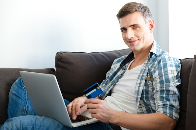 Szczęśliwy przystojny mężczyzna korzystający z laptopa i karty kredytowej oraz robiący zakupy w internecie siedząc w domu