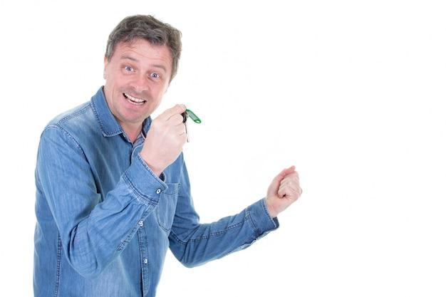 Szczęśliwy przystojny mężczyzna pokazuje klucze od domu do domu