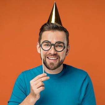 Szczęśliwy przystojny mężczyzna pozuje w fałszywych okularach