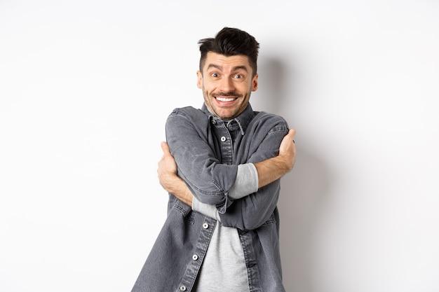 Szczęśliwy przystojny mężczyzna przytula się i uśmiecha się, obejmując własne ciało, stojąc na białym tle w szarej kurtce.
