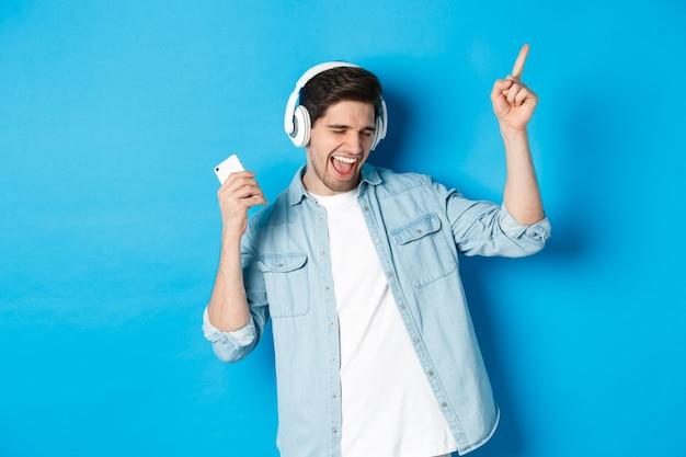 Szczęśliwy przystojny mężczyzna tańczy, słucha muzyki na smartfonie w słuchawkach, stojąc na niebieskim tle