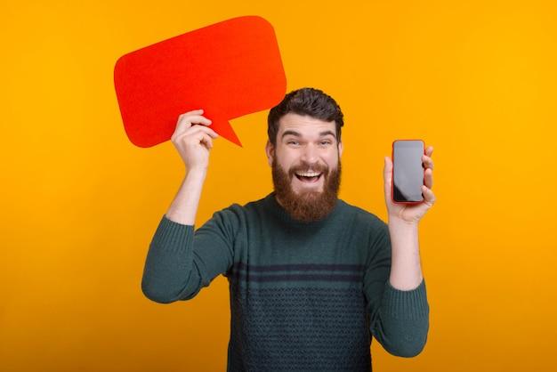 Szczęśliwy przystojny mężczyzna trzyma czerwonego mowa bąbel i pokazuje smartphone ekran, najlepsza oferta