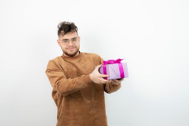 Szczęśliwy przystojny mężczyzna trzyma jego świąteczny prezent na białym.