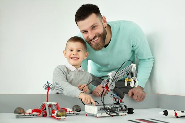 Szczęśliwy przystojny mężczyzna uśmiecha się do kamery z jego wesołym młodym synem podczas wspólnej zabawy samochodami