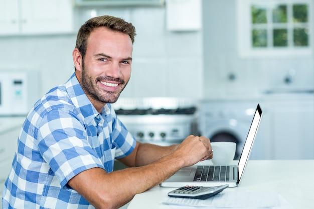 Szczęśliwy przystojny mężczyzna używa laptop przy stołem w kuchni