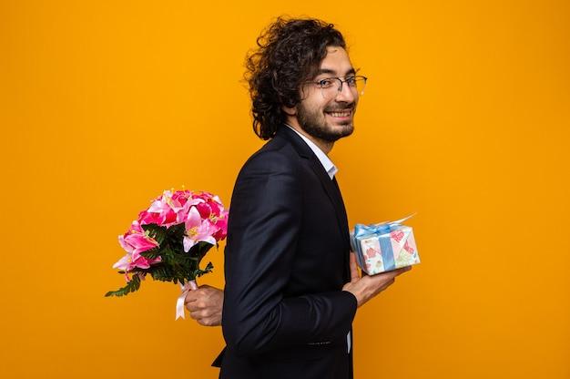 Szczęśliwy przystojny mężczyzna w garniturze trzyma prezent chowając bukiet kwiatów za plecami idą do świętowania międzynarodowego dnia kobiet 8 marca stojąc na pomarańczowym tle