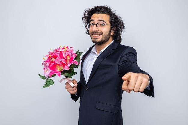 Szczęśliwy przystojny mężczyzna w garniturze z bukietem kwiatów, uśmiechając się wesoło, wskazując palcem wskazującym