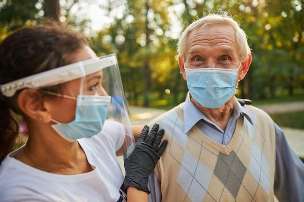 Szczęśliwy przystojny mężczyzna w masce ochronnej z pracownikiem socjalnym na ulicy miasta