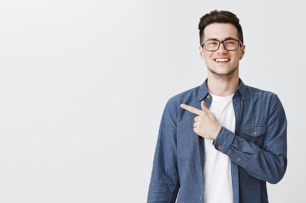Szczęśliwy przystojny mężczyzna w okularach palcem wskazującym w lewo