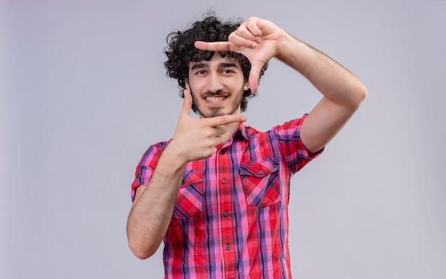 Szczęśliwy przystojny mężczyzna z kręconymi włosami w kraciastej koszuli co rama z rękami i palcami