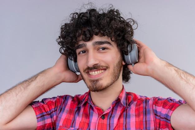 Szczęśliwy przystojny mężczyzna z kręconymi włosami w kraciastej koszuli w słuchawkach z uśmiechem