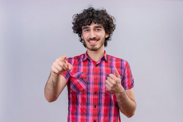 Szczęśliwy przystojny mężczyzna z kręconymi włosami w kraciastej koszuli, wskazując na aparat