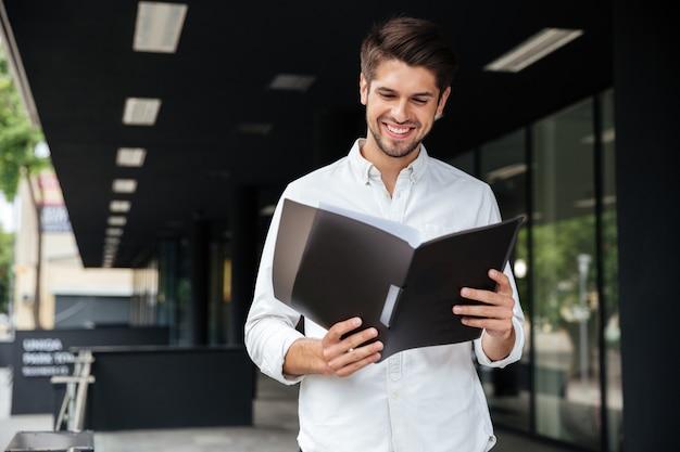 Szczęśliwy przystojny młody biznesmen stojący i przeglądający dokumenty w folderze