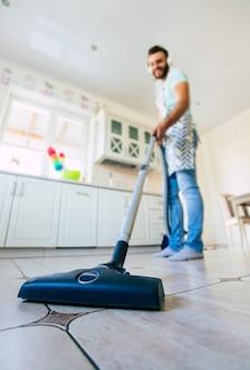 Szczęśliwy przystojny młody brodacz czyści podłogę w domowej kuchni i dobrze się bawić.