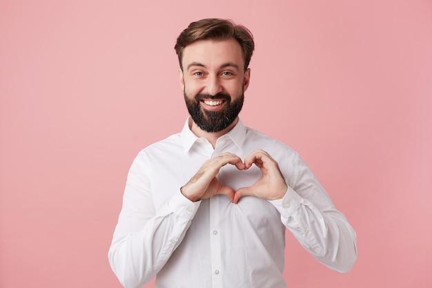 Szczęśliwy przystojny młody brodaty mężczyzna z krótkimi brązowymi włosami składane serce z uniesionymi rękami