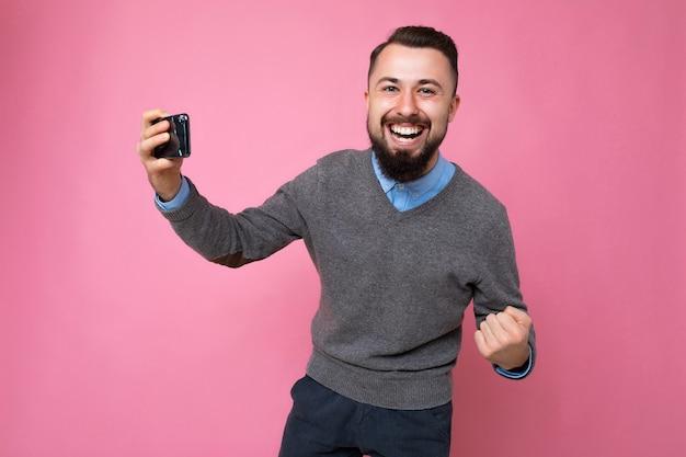 Szczęśliwy przystojny młody brunetka nieogolony mężczyzna z brodą ubrany na co dzień w szary sweter i niebieską koszulę
