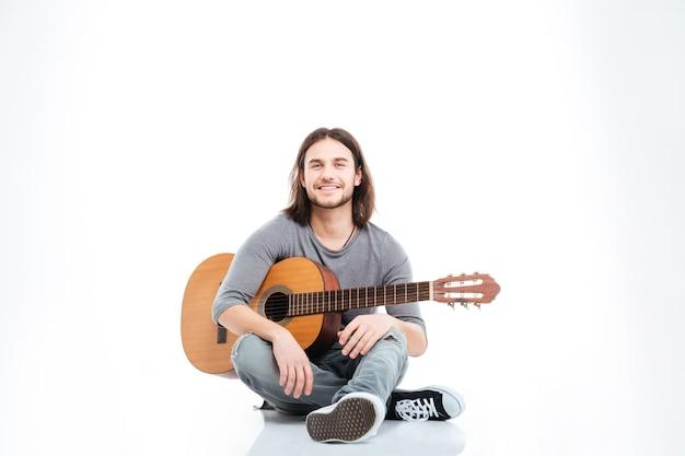 Szczęśliwy przystojny młody człowiek z długimi włosami siedzi na podłodze z gitarą na białym tle