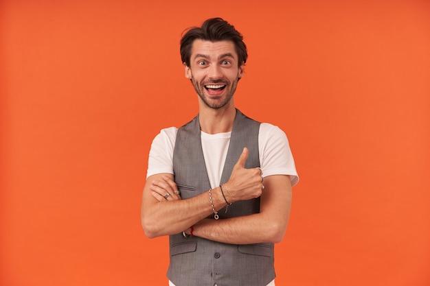 Szczęśliwy przystojny młody człowiek z włosia trzymać ręce złożone i pokazywać kciuki do góry
