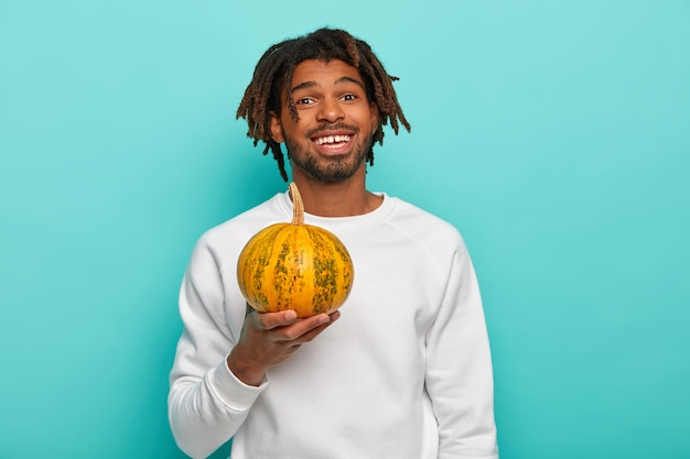 Szczęśliwy przystojny młody facet rasy mieszanej z dredami, trzyma małą dojrzałą żółtą dynię, zamierza zrobić dietetyczną sałatkę, ubrany w strój codzienny