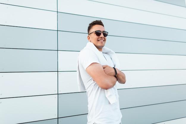 Szczęśliwy przystojny młody hipster mężczyzna w modnej białej koszulce w stylowe okulary przeciwsłoneczne z modną fryzurą pozuje w pobliżu nowoczesnego budynku