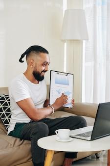 Szczęśliwy przystojny młody mężczyzna pokazujący wykres w dłoniach koledze siedzący w domu przed laptopem i uczestniczący w konferencji online