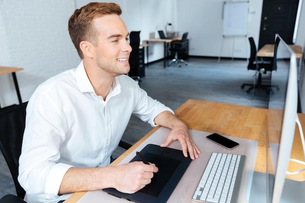 Szczęśliwy przystojny młody mężczyzna projektant przy użyciu komputera i