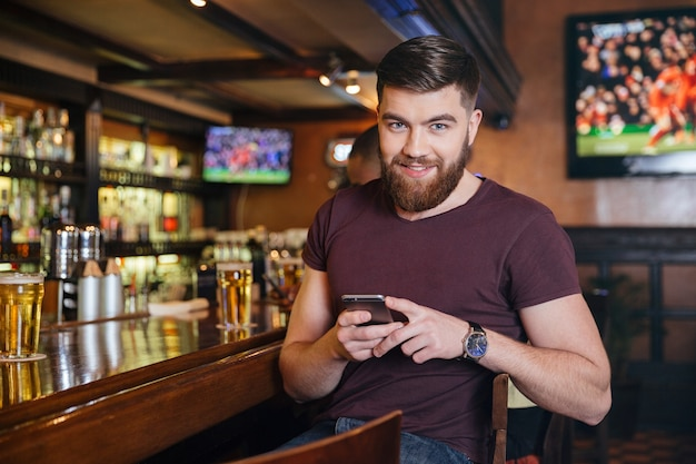Szczęśliwy przystojny młody mężczyzna siedzi i używa telefonu komórkowego w pubie